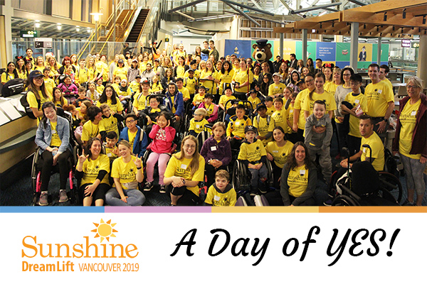 Hundreds of Sunshine kids and volunteers in yellow shirts posing for group photo at airport