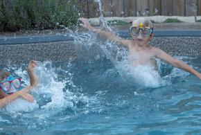 Two kids in goggles splash in a pool