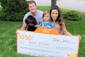 Mike and family kneel on lawn holding oversized lottery cheque